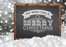 Wij wensen u Vrolijke Kerstmis op bord met blurrbos en sneeuw Stock Afbeelding