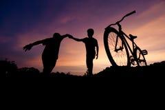 Wijd bewegende silhouetten van twee jongens die handen houden stock afbeeldingen