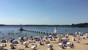 Wijd geschoten van mensen die en van bij Wannsee-Strand een hete dag in de Zomer genieten zwemmen stock videobeelden