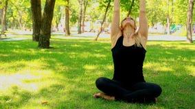 Wijd geschotene Jonge vrouw die yoga in park doen stock videobeelden