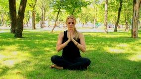 Wijd geschotene Jonge vrouw die yoga in park doen stock video