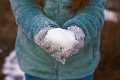 Wijfje in Blauw de Winterjasje en Grey Mittens, die een Sneeuwbal houden Stock Fotografie
