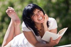 Wijfje dat in een park met een boek lacht Stock Afbeeldingen