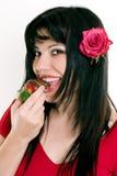Wijfje dat verse aardbeien in chocolade eet stock foto
