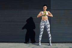 Wijfje in de holdingsgewichten van het trainingtoestel met haar handen samen Stock Foto's