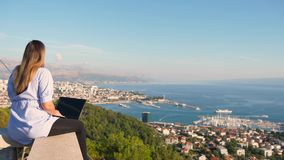 Wijfje die aan laptop bovenop de Marjan-heuvel in Spleet werken, Kroatië stock footage