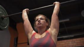 Wijfje die barbell de oefening van de duwpers in gymnastiek doen stock video