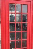 Wijfje die in Britse Rode PhoneBox telefoneren stock afbeeldingen