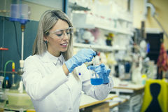 Wijfje die in chemielaboratorium werken Stock Foto
