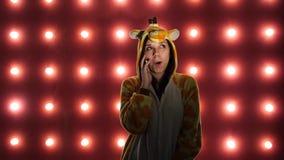 Wijfje die de telefoon uitnodigen Vrouw in kostuum van giraf op rode achtergrond met gloeilampen stock video