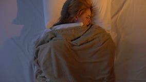 Wijfje die en in bed werpen het draaien, schuint buiten in slaap het vallen af wegens lawaai stock video