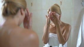 Wijfje die en gezicht met bevochtigende lotion masseren afromen, home spa behandeling stock videobeelden