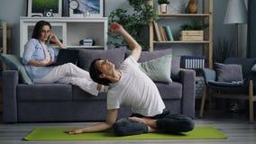 Wijfje die freelancer thuis gebruikend laptop die wanneer echtgenoot die yoga doen roepen werken stock footage
