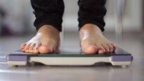 Wijfje die gewicht op gezondheidsschaal meten stock videobeelden