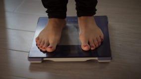 Wijfje die gewicht op gezondheidsschaal meten stock video