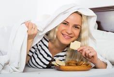 Wijfje die in het geheim koekjes in bed eten royalty-vrije stock afbeeldingen