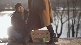 Wijfje die hete koffie met de dakloze mens delen stock footage