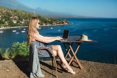 Wijfje die met haar laptop dichtbij het overzees werken stock foto