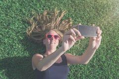 Wijfje die op gras liggen en selfie met haar slimme telefoon nemen stock fotografie