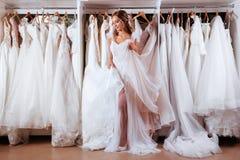 Wijfje die op huwelijkskleding proberen stock foto's