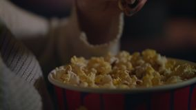 Wijfje die popcorn van document emmerclose-up met de hand plukken Het eten van pop graan bij bioskoop stock footage