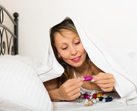 Wijfje die snoepjes in bed eten stock afbeeldingen