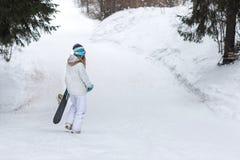 Wijfje die snowboarder met snowboard in koud de winterweer er vandoor gaan Royalty-vrije Stock Foto's