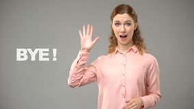 Wijfje die tot ziens in gebarentaal, tekst op achtergrond, mededeling voor doof zeggen stock footage