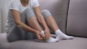 Wijfje die twee-riem enkelomslag toepassen, die voet aan oedeem na sporttrauma lijden stock video