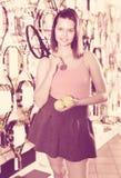 Wijfje die zich in sportieve goederenopslag bevinden met ballen en racket Stock Foto