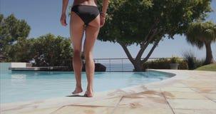 Wijfje die in zwempak in de pool lopen stock footage
