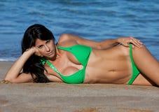 Wijfje in een groene bikini op het zand Stock Afbeeldingen