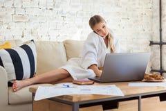 Wijfje freelancer in een witte laagkleding die remotly van haar eettafel in de ochtend werken Huizen op een bank op a Stock Afbeelding