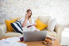 Wijfje freelancer in een witte laagkleding die remotly van haar eettafel in de ochtend werken Huizen op een bank op a Royalty-vrije Stock Afbeelding