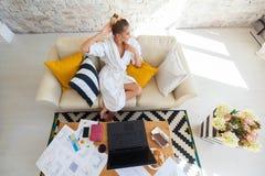 Wijfje freelancer in een witte laagkleding die remotly van haar eettafel in de ochtend werken Huizen op een bank op a Royalty-vrije Stock Fotografie
