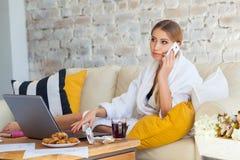 Wijfje freelancer in een witte laagkleding die remotly van haar eettafel in de ochtend werken Huizen op een bank op a Stock Fotografie