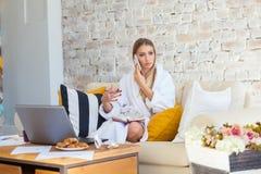 Wijfje freelancer in een witte laagkleding die remotly van haar eettafel in de ochtend werken Huizen op een bank op a Royalty-vrije Stock Foto