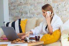 Wijfje freelancer in een witte laagkleding die remotly van haar eettafel in de ochtend werken Huizen op een bank op a Stock Foto