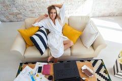 Wijfje freelancer in een witte laagkleding die remotly van haar eettafel in de ochtend werken Huizen op een bank op a Stock Foto's