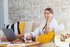 Wijfje freelancer in een witte laagkleding die remotly van haar eettafel in de ochtend werken Huizen op een bank op a Royalty-vrije Stock Foto's