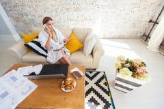 Wijfje freelancer in een witte laagkleding die remotly van haar eettafel in de ochtend werken Huizen op een bank op a Royalty-vrije Stock Afbeeldingen