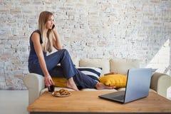 Wijfje freelancer in haar toevallige huiskleding die remotly van haar eettafel in de ochtend werken Huizen op een bank  Stock Foto's