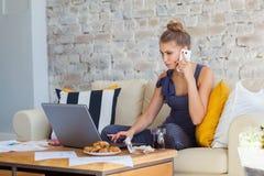 Wijfje freelancer in haar toevallige huiskleding die remotly van haar eettafel in de ochtend werken Huizen op een bank  Royalty-vrije Stock Afbeelding
