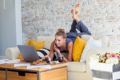 Wijfje freelancer in haar toevallige huiskleding die remotly van haar eettafel in de ochtend werken Huizen op een bank  Royalty-vrije Stock Foto