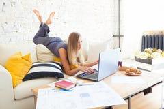 Wijfje freelancer in haar toevallige huiskleding die remotly van haar eettafel in de ochtend werken Huizen op een bank  Stock Afbeelding