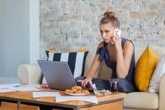 Wijfje freelancer in haar toevallige huiskleding die remotly van haar eettafel in de ochtend werken Huizen op een bank  Stock Foto
