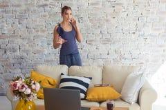 Wijfje freelancer in haar toevallige huiskleding die remotly van haar eettafel in de ochtend werken Huizen op een bank  Royalty-vrije Stock Fotografie