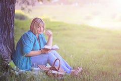 Wijfje in het park op zonsondergang met boek Royalty-vrije Stock Fotografie