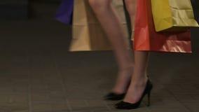 Wijfje in hoge hielen die het winkelen zakken dragen, die showcase, verslaving naderen stock video
