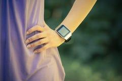 Wijfje met haar handen op heupen die slim horloge dragen stock afbeelding